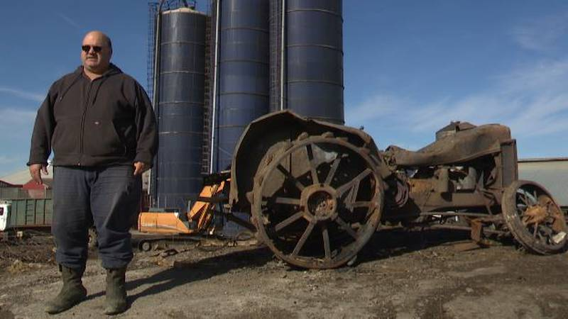 Bill Eastman stands with a tractor burned in the fire