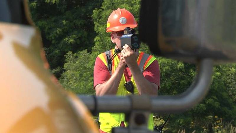 Trooper dressed in construction garb holds a speed gun as part of Operation Hardhat