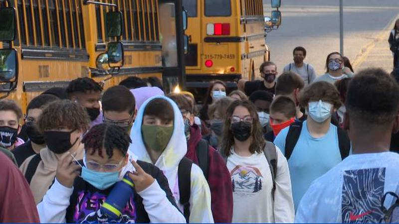 Masked students leave their buses to enter the school building