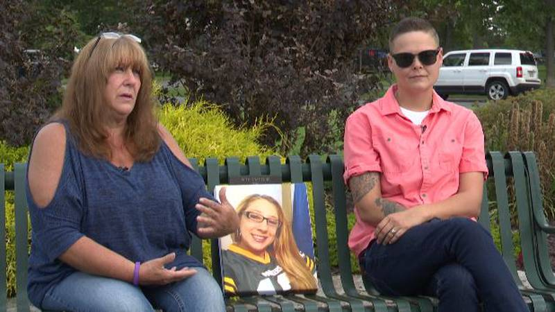 Roxanne George and Desiree Smith with a photo of Tia George-Sargent