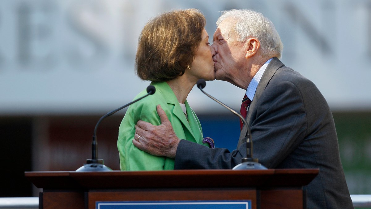 FILE - This Oct. 1, 2009 file photo shows former President Jimmy Carter getting a kiss from his...