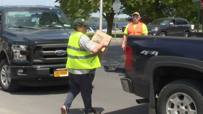 A volunteer loads food Tuesday at a food distribution in Ogdensburg.