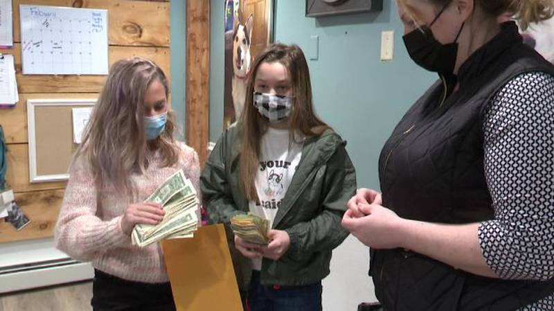 Avery Carlin and Annalyse Sinitiere present money to the SPCA