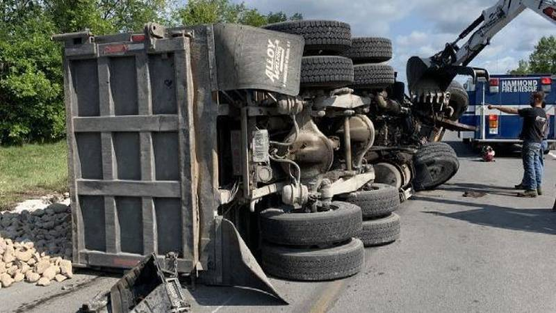 Two people were hurt and a dump truck loaded with rocks overturned after colliding with an SUV...